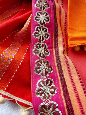 Close-up of  gold, floral sequence jari border on grey, orange and red striped, flat-weave, Indian cotton throw