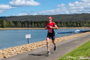 Images shows a man wearing a cap running in front of a lake on a sunny day.