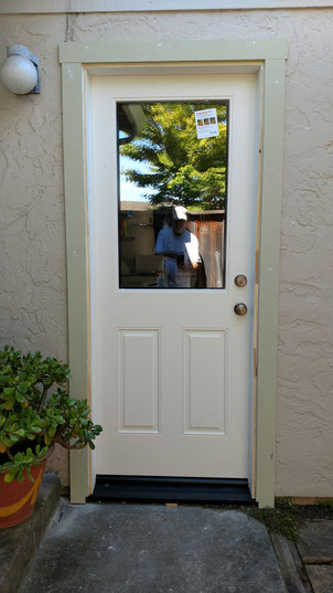 After prehung fiberglass flush glazed 1/2 lite door installation, stucco wall, unpainted