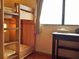 個室は2段ベッド1台とデスクを備えています。