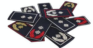 Mherere Funktionsabzeichen für verschiedene Dienstgrade. Teilweise mit ein bis drei Sternen in silber oder gold, sowie mit Eichenlaub in silber, gold oder rot.