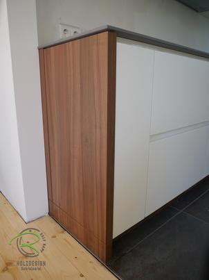 Moderne Küche in weiß und Nussbaumdekor von Schreinerei Holzdesign Ralf Rapp in Geisingen mit Eck-Stauraumlösung im Unterschrank für Handstaubsauger mit Ladestation
