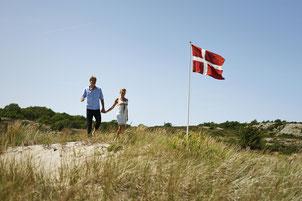 Dänemarks Nationalflagge weht gern in den Dünen – der Dannebrog auf Bornholm. Foto: VisitDenmark/Niclas Jessen
