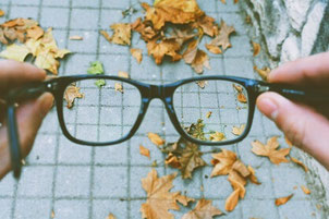 A pair of glasses held out in front of a person's eyes. The ground is covered in bricks with leaves on top. Taken together with the text, the image suggests that mindfulness helps people gain fresh perspective on everyday life.