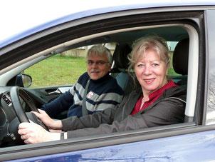 im Auto sind Fahrlehrer Rainer mit zufriedener Auffrischlerin am Steuer zu sehen
