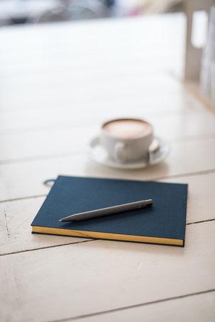 Buch mit Stift und Tasse Kaffee im Hintergrund