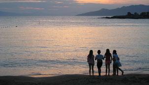 Kinder spielen am Strand bei Sonnenuntergang. Kinderbetreuung Koroni Griechenland