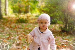 Ein kleines Mädchen, umgeben von buntem Herbstlaub, schaut mit frechem Schmollmund in die Kamera.