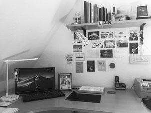 Schreibtisch und Arbeitsplatz mit Fotos und Postkartenwand