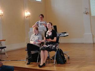 Das Foto zeigt Frau Schachler am Rednerpult. Sie hält den Teilhbabeplan in der Hand. Vor ihr sitzen 2 Gebärdensprach-Dolmetscherinnen.