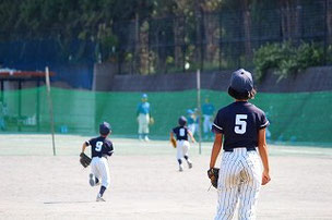 打球を追いかけるちびっ子たち。見守る投手。