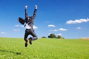 Erfolg Businesserfolg Mann springt über eine Wiese
