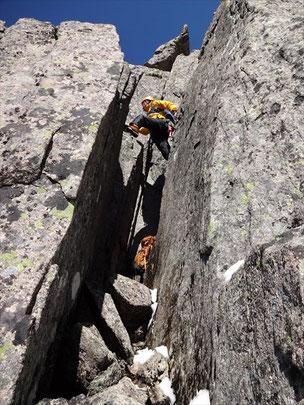 チムニーに入り込み、右へ回り込むと階段状になっていて、そこから隣の岩へ大股開きで超える