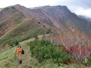 いくつものピークを通る登山道をバックに写真を撮る