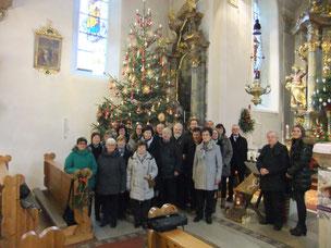 Der derzeit gesamt 22köpfige Kirchenchor Pittersberg zusammen mit  Initiator Pfarrer Josef Fromm (2.von rechts) und Chorleiterin Karin  Hottner (rechts) unter dem Weihnachtsbaum am Chrsittag 2017 in der Nikolauskirche nach der gesungenen Messe