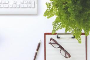 1週間のタイムスケジュール表、メモ帳がデスクにある。日常の業務内容を社長と後継者で共有する。