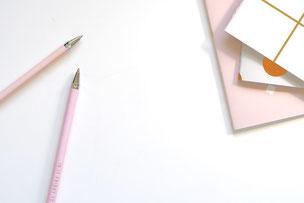 デスクの上にノートが3冊積み重ねられている、傍らにピンクのボールペンが2本。