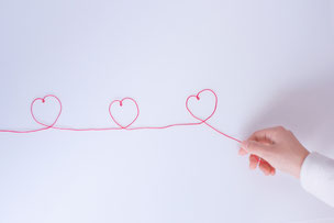 赤い毛糸を持つ指先。毛糸でハート形3つ。