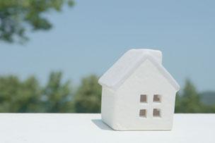 青空と緑がのぞく窓辺に飾られた白のミニチュアハウス。