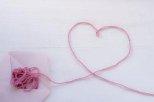 ピンクの封筒から飛び出したピンクの毛糸。ハートの形をつくっている。