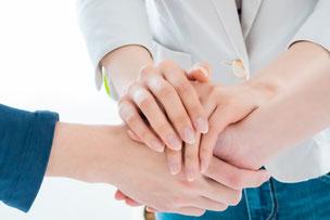 握りあう手。観葉植物の鉢植え。