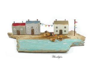 Treibholz, Strandhäuser mit Wimpelkette am Meer mit kleinen Booten und Anker