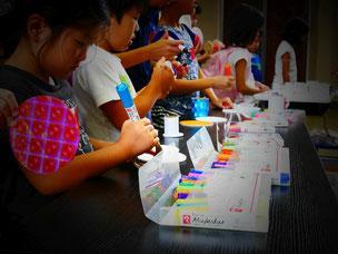 両輪となる円台紙に、思い思いの絵を描く子どもたち。