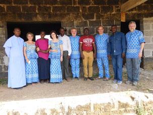 Reisegruppe mit  Einheimischen vor dem Schulhaus - Rohbau