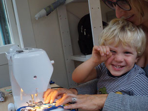 Owner sewing in her studio with her son on her lap