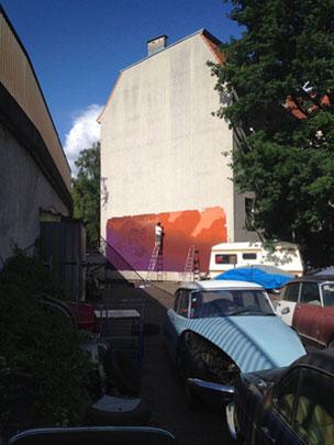 Im Anschnitt sieht man die U-Bahn Trasse und im Hintergrund steht ein Graffiti Sprüher auf einer Leiter an der Fassade. Ein blauer Himmel, ein grüner Baum und vielen alte Autos sind zu sehen.