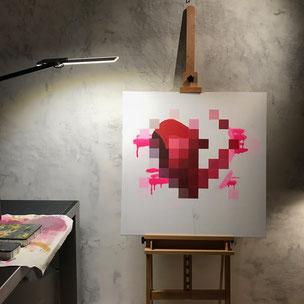 Eine Leinwand mit weißem Hintergrund mit einem verpixelten, roten Herz aus einem Ballon und einem Boxhandschuh. Im Hintergrund sind neon pinke Sprühdose Striche zu sehen. An einigen wenigen Stellen ist der Ballon nicht verpixelt und man sieht Graffiti