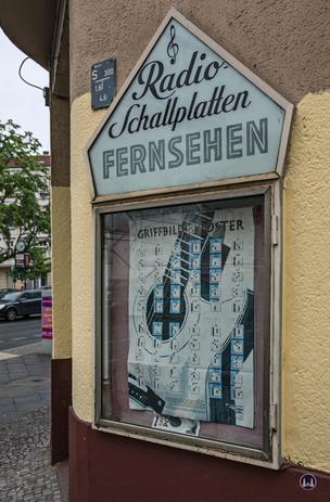 Musikhaus Bading in Berlin - Neukölln, Karl - Marx - Straße. Leuchtkasten im expressionistischen Stil.