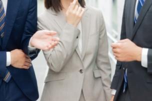 談笑するスーツ姿のビジネスパーソン男女3人。