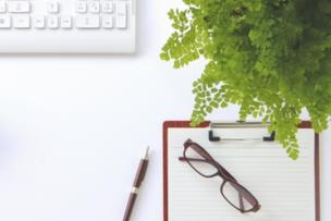 パソコンのキーボード。赤のバインダーファイル。リーディンググラス。ボールペン。観葉植物のグリーン。