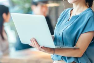 オフィスで打ち合わせ中のビジネスパーソン。広げたノートパソコンを抱える女性。水色のブラウス。