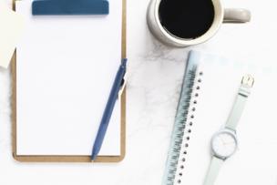 リングノートの上に置かれた水色の腕時計。メモパッドとボールペン。コーヒーの入ったマグカップ。