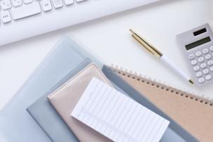パソコンのキーボードの前に置かれたファイル、リングノート、手帳、メモパッド。ボールペンと電卓。
