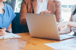 明るいオフィスのテーブルでミーティングするビジネスパーソン。ノートパソコンと資料。