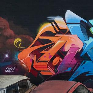 Ein Hinterhof, gelegen an der Hamburger U-Bahn U3. Im Vordergrund sieht man alte kaputte Autos und im Hintergrund ein buntes Graffiti gemalt auf einer schwarzen Wand.