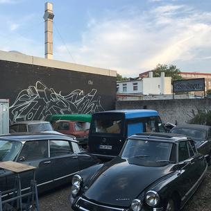 Ein Hinterhof mit alten Citroens. Im Hintergrund ist ein angefangenes Graffiti zu sehen von Ohm One.