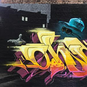 Auf einer Fassade steht in großen gelb und pinken Graffiti Buchstaben der Name Ohm. Im Hintergrund ist eine Stadt bei Nacht zusehen und über den Buchstaben ein unsichtbarer Mann. Man sieht nur seine Brille, Handschuh und Cap.