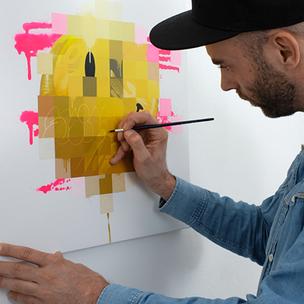 Der Graffiti Sprüher Ohm One steht mit einem Pinsel in der Hand vor einer Leinwand. Er trägt einen blaues Jeans Hemd und trägt  ein schwarzes Cap