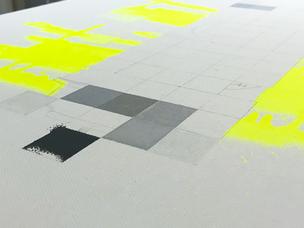 Eine unfertige Leinwand mit neon gelber Farbe und grauen Pixeln. Auf der Leinwand sind Bleistift Linien zu sehen.