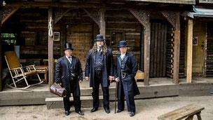 """Achim Bunde (50, Mitte) alias """"Hunter Hank"""" mit zwei Mitstreitern im historischen Outfit vor der Bank der Radebeuler Westernstadt """"Fort Henry"""" (Foto: Bild)"""