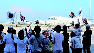 出発する哨戒機「P―3C」と見送る家族ら。夏休み期間中のためか、平日の朝にも関わらず多くの子どもらが参加。日の丸を振って、送り出した=26日、那覇基地