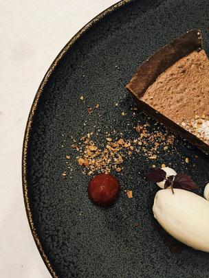 Chocoladetaart o.b.v. zwarte chocolade, vergezeld door een bolletje witte chocolade ijs, een crème fraîche van mascarpone en een crumble van amandel en cacao.