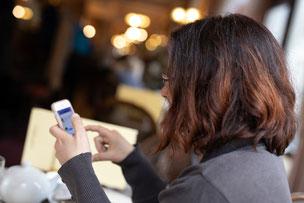 Conny, Mindset-Coach für Frauen, erwartet auf ihrem Handy Deine Kontaktaufnahme.