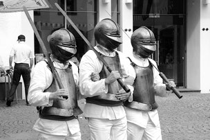 Drei Menschen in Rüstungen mit Iserköppen