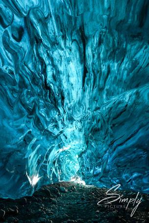 Intensiv schimmerndes blaues Licht im Eis, schwarze Einschlüsse von vulkanischer Asche oder Gestein