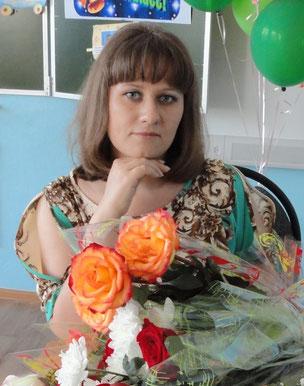 Наталия Александровна Федорова с букетом розовых роз в кабинете начальных классов